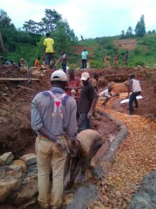 In Burundi, Africa is building a small dam at a natural spring.